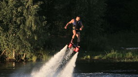 Fly board rider. Man on the flying board on the river, water jet spray.Man on the flying board flies over the lake water.Fly board rider stock video footage