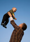 Fly boy. The happy daddy lifts on hands of the little son against the blue sky Royalty Free Stock Images