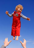Fly boy. Father throwing up his son. Blue sky on the background stock photos