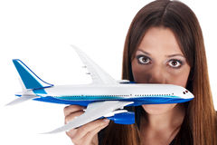 Fly fear. Metaphor by woman holding airplane in hand stock photography