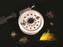 Fly-fish. A fly fishing reel and flies on a black background royalty free stock photo