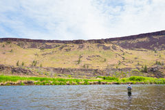 Fly Fisherman Casting on the Deschutes River. Experienced fly fisherman fishing the Deschutes River in Oregon, casting for fish while standing in the water stock photography