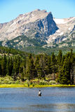 Fly fisherman fishing in lake in Rocky Mountain National Park Royalty Free Stock Image