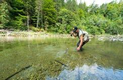 Fly fisherman flyfishing in river Stock Image