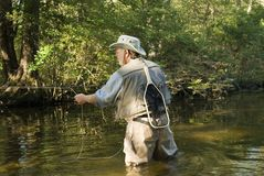 Fly fisherman with net. An elderly fly fisherman wearing hat, waders and holding a fishing rod, has a net hanging from his vest. He is standing in a river/stream royalty free stock photography
