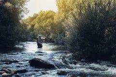 Fly fisherman using flyfishing rod. Fly fisherman using flyfishing rod in beautiful river Stock Image