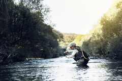 Fly fisherman using flyfishing rod. Royalty Free Stock Images