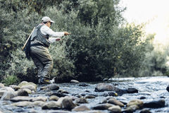 Fly fisherman using flyfishing rod. Royalty Free Stock Photography