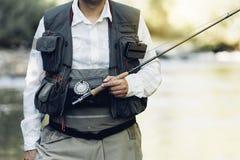 Fly fisherman using flyfishing rod. Fly fisherman using flyfishing rod in beautiful river Stock Photos