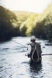 Fly fisherman using flyfishing rod. Fly fisherman using flyfishing rod in beautiful river Royalty Free Stock Photo