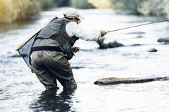 Fly fisherman using flyfishing rod. Fly fisherman using flyfishing rod in beautiful river Stock Photo