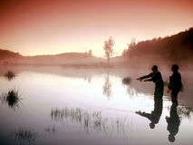 Fly Fishing. Two fishermen in lake fly  fishing at sunrise Royalty Free Stock Photo