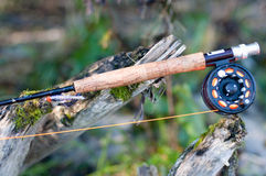 Fly fishing rod and reel. Closeup of fly fishing rod and reel on wooden branch Stock Photos