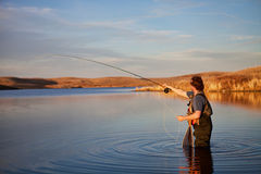 Fly fishing. Fly fisherman casting in a lake in golden light Stock Photo