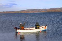Fly fishing. Two men fly fishing in a small boat Stock Photo