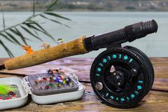 Fly fishing box flies on a wooden platform on the river. Spinning, fly fishing on a wooden table royalty free stock photos