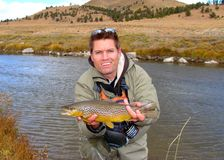 Fly fishing - fisherman holding fish Stock Images