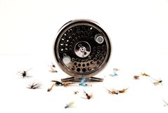 Fly fishing gear. A metal fly fishing reel with some artificial flies Stock Image