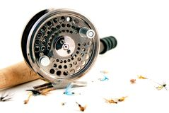 Fly fishing gear. A metal fly fishing reel with some artificial flies and rod Stock Photography