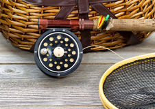 Fly Fishing Gear with Creel. Antique fly fishing reel, rod, landing net, creel and artificial flies on rustic wood. Layout in horizontal format Royalty Free Stock Images