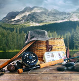 Fly fishing gear on wooden deck with lake Stock Images