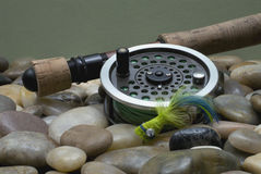 Fly Fishing III. Fly fishing rod and reel with a green popping bug stock photos