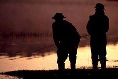 Fly fishing men 02. Two men fly fish on a river or lake; silhouette Stock Image