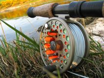 Fly Fishing Reel. A fly fishing reel and rod by the River Tweed, Scotland royalty free stock photo