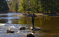 Fly fishing on a rock. A fisherman standing on a rock in river, fly fishing Royalty Free Stock Photo