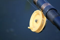 Fly fishing rod on blue background close Stock Images