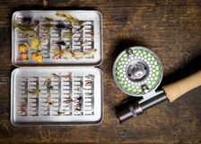 Fly fishing rod and case of flies. Fly fishing gear, which includes a reel, pole, and containers of flies Stock Images