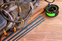 Fly fishing rod with a coil and flies lie on old, wooden boards stock image