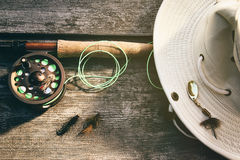 Fly fishing rod with hat on wood Stock Photo