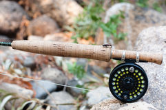 Fly fishing rod, reel and fly. Fly fishing rod with reel and fly on white stone Stock Photo