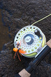 Fly Rod and Spider Fly on a Wet Rock. Fly Fishing Rod and Spider Fly on a Wet Rock Stock Photo