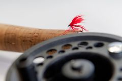 Fly fishing fly on the rod on white background. Reel and vintage royalty free stock images