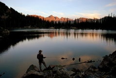 Fly fishing at sunset. A person is silhouetted against a glassy lake as they fly fish at sunset.  Mountains turned red by alpenglow are seen in the distance and Stock Photo