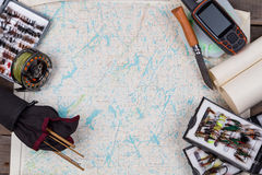 Fly-fishing tackles on paper map background Royalty Free Stock Photo