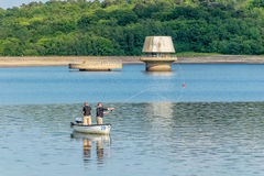 Fly fishing for trout on Bewl Water resevoir. These two men in their little boat are fly fishing for trout in the man-made reservoir at Bewl Water, Kent Royalty Free Stock Photo