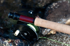 Fly fishing vintage reel and rod in water Stock Image