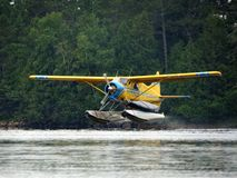 Fly-In Float Plane. A float plane takes off from a northern Minnesota lake with a canoe on board for some remote fishing Stock Photos