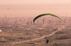 Fly freely in the sky. Paragliding is a sky sport. A paragliding can carry one or two people. You float in the air but the paragliding are for slowing down the Stock Images
