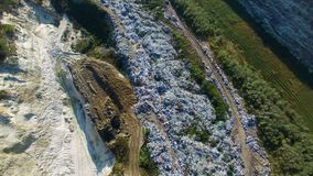 Fly about garbage dump. Excavator working on the ground. Aerial view stock video footage
