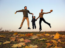 Fly happy family with autumn leaves. Sundown royalty free stock photography