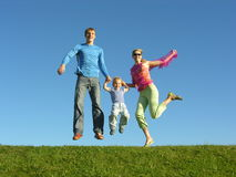 Fly happy family on blue sky. Jump royalty free stock photography