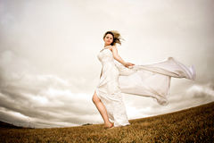 Fly happy woman. Runaway bride in the field during a stormy windy day Stock Photography