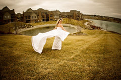 Fly happy woman6. Runaway bride in the field during a stormy windy day Stock Photography