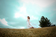 Fly happy woman9. Runaway bride in the field during a stormy windy day royalty free stock photo
