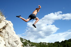 Fly Like An Eagle. A young man jumps from a cliff into the sea Stock Image