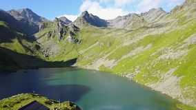Fly over mountain lake and cabin, Switzerland stock video footage